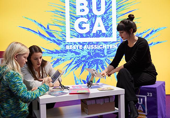 Das Bild zeigt Besucher am Stand der Bundesgartenschau Mannheim 2023 gGmbH am 06. Januar 2020. Drei Personen sitzen an einem Tisch und tippen auf iPads, im Hintergrund ist das BUGA Logo zu sehen.