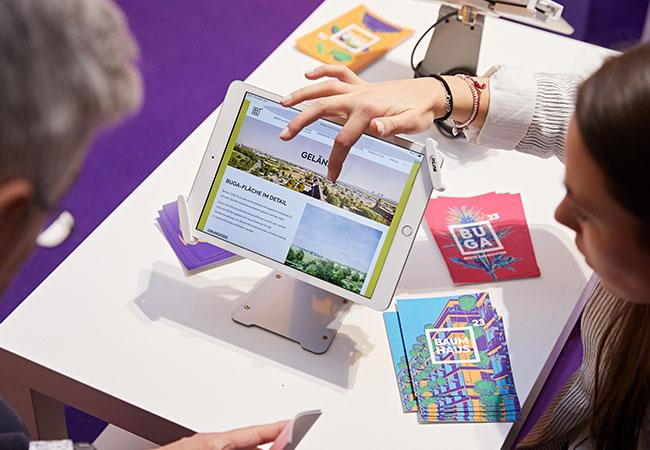 Das Bild zeigt einen Bildausschnitt des Messestandes der BUGA gGmbH auf dem Neujahrsempfang. Im Vordergrund ist ein iPad zu sehen auf dem die Website der BUGA abgebildet ist. Eine Mitarbeiterin der BUGA erklärt einem Gast die Infos der Website.