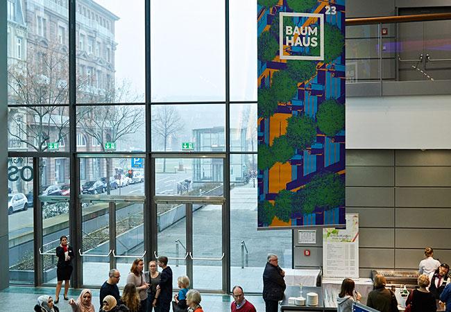 Blick von der Rolltreppe in das Foyer des Rosengartens. Von der Decke hängen große Banner der Bundesgartenschau Mannheim 2023 gGmbH.