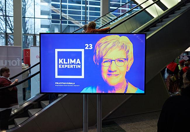"""Das Bild zeigt einen Fernseher im Rosengarten Mannheim. Auf dem Bildschrim ist Bürgermeisterin Kubala zu sehen. Neben ihr ist das typische BUGA Quadrat mit den Worten """"Klimaexpertin"""" abgebildet."""
