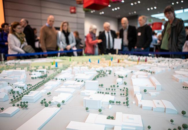 Nahaufnahme des Spinelli Modells auf dem Neujahrsemfpang der Stadt Mannheim. Im Hintergrund stehen interessierte BesucherInnen um das Modell verteilt.