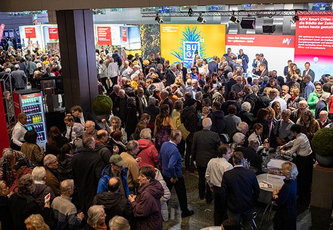 Blick auf das Foyer des Rosengartens und den BUGA Messestand auf dem Neujahrsempfang. Die Halle ist durch viele Besucherinnen und Besucher gefüllt