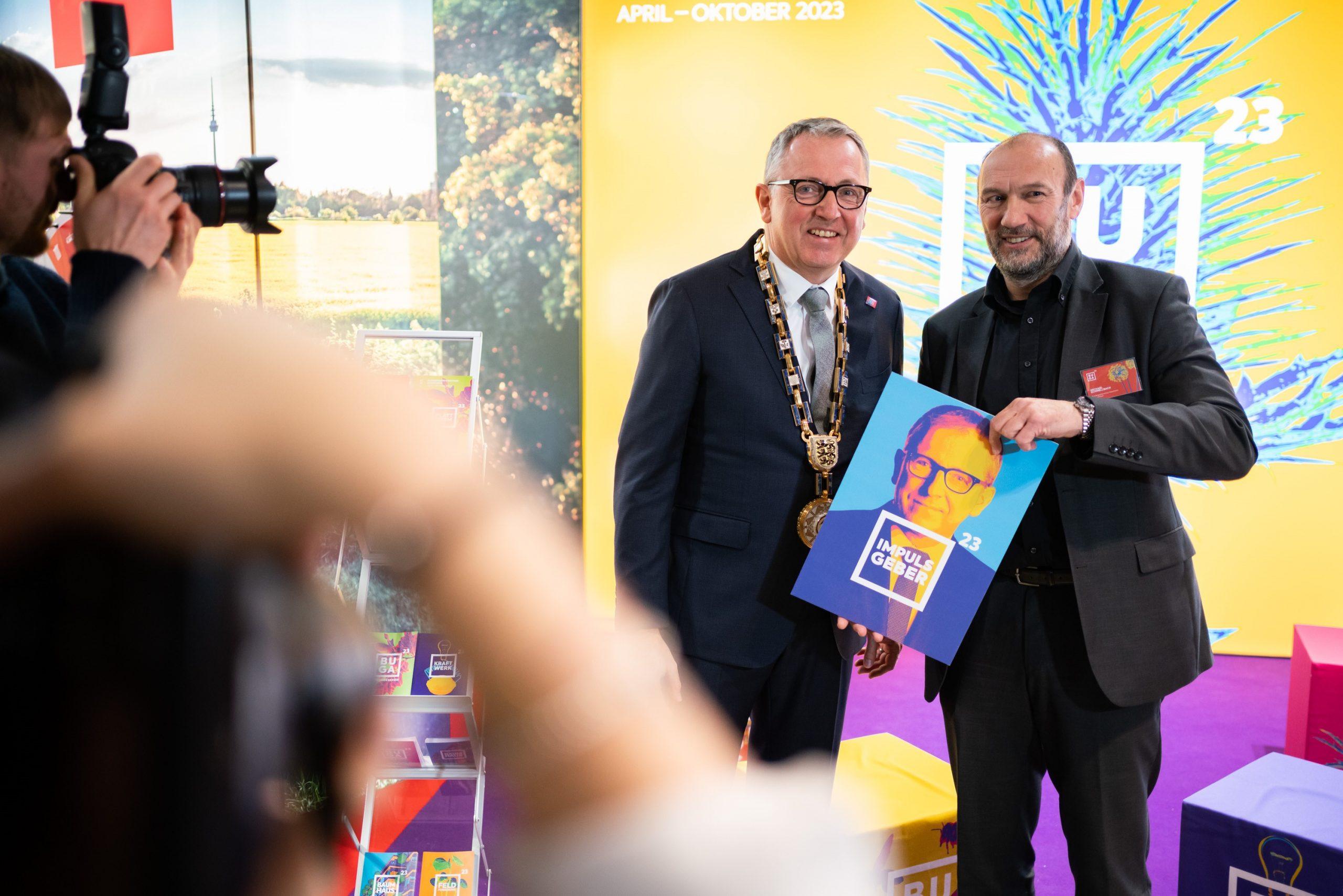Das Foto zeigt DR. Peter Kurz, Oberbürgermeister der Stadt Mannheim, und Michael Schnellbach, den Geschäftsführer der BUGA, vor dem Messestand der BUGA 23.