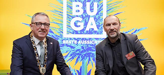 Das Bild zeigt v. l. n. r. Oberbürgermeister Dr. Kurz und Michael Schnellbach. Im Hintergrund ist das neue BUGA Logo zu sehen.