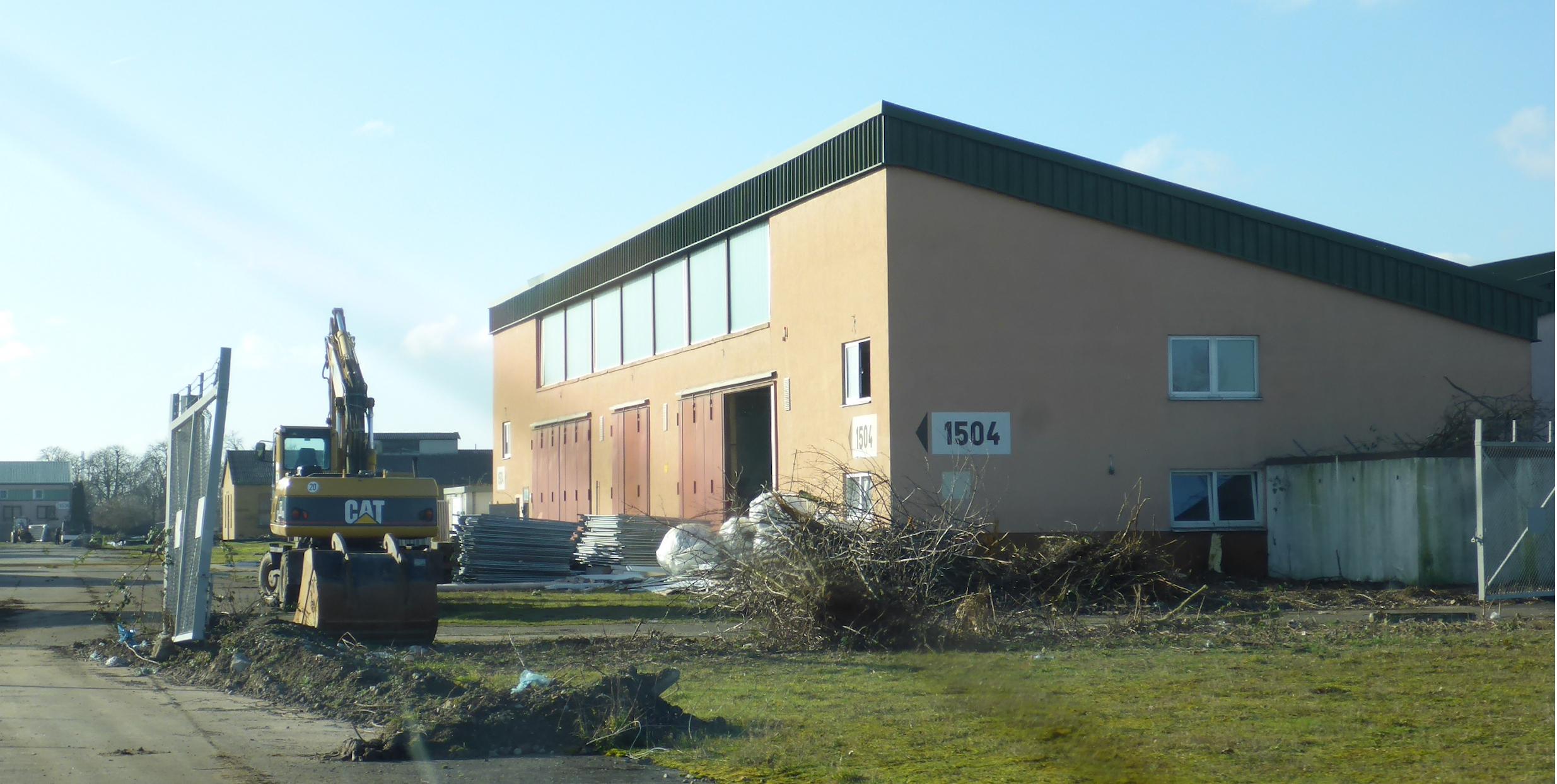 Blick auf eine Halle auf Spinelli. Vor der Halle sind Bauzäune aufgestellt.
