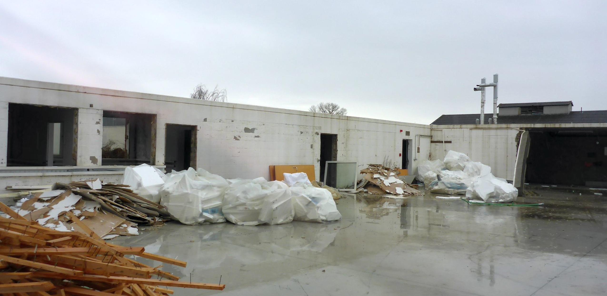 Das Bild zeigt eine halb abgerissene Halle auf Spinelli. Der Bauschutt ist nach Materialien sortiert.