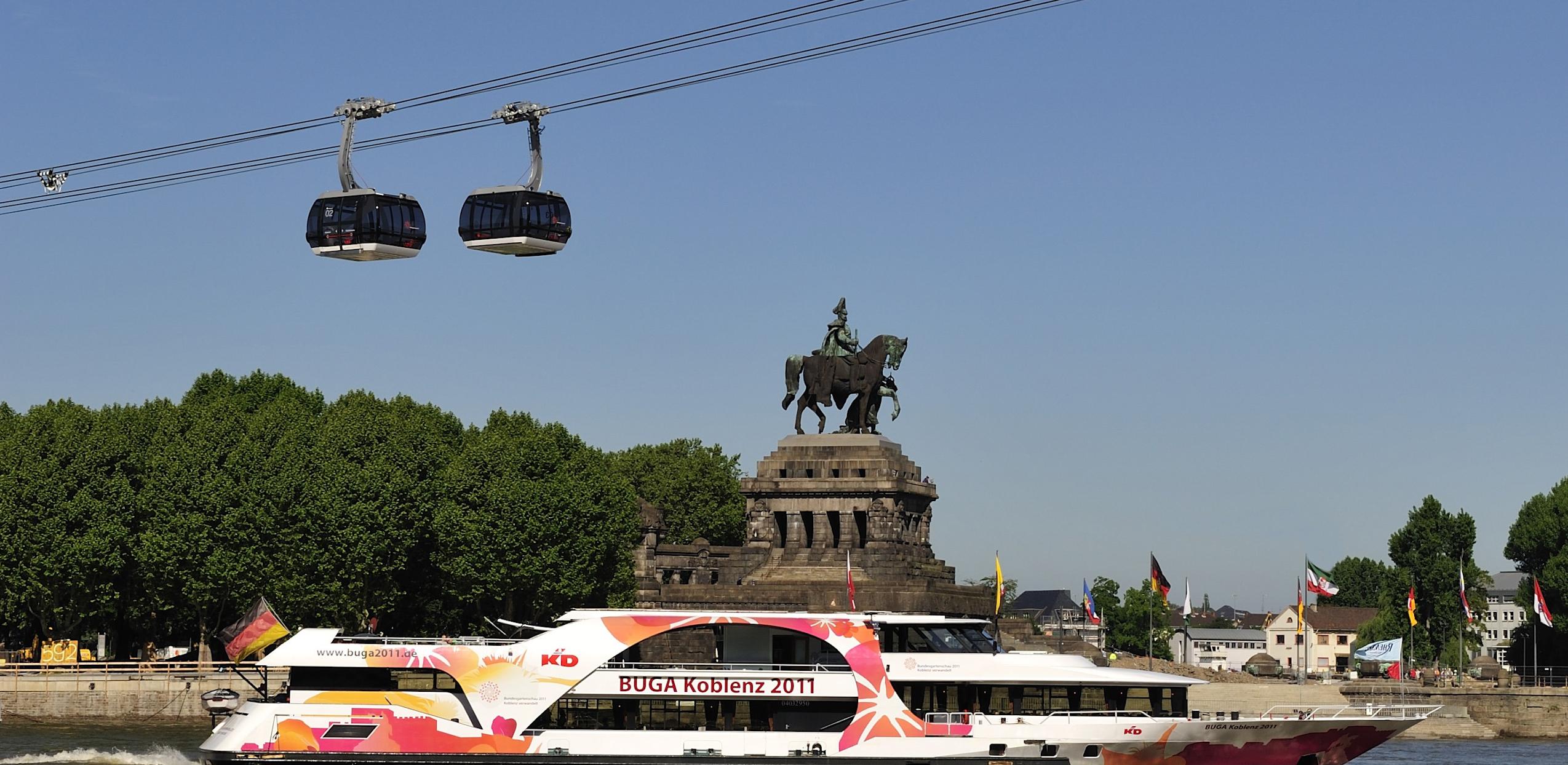 Blick auf das Kaiser-Wilhelm-Denkmal am Deutschen Eck. Auf dem Rhein fährt ein BUGA Koblenz Passagierschiff und zwei Gondeln der Seilbahn..