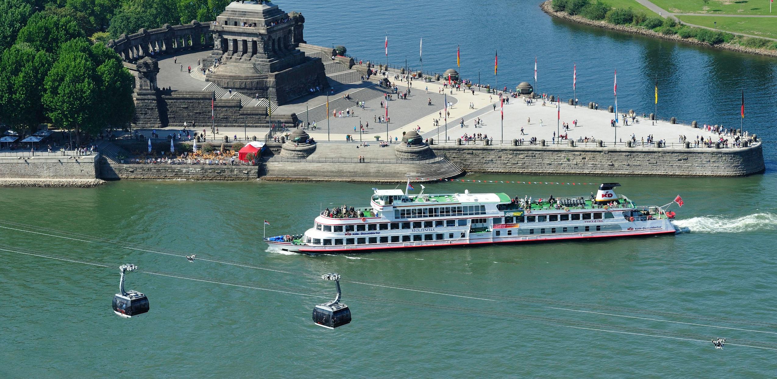 Blick von der Festung Ehrenbreitstein auf das deutsche Eck (Koblenz). Man sieht zwei Gondeln der Seilbahn und ein Besucherschiff auf dem Rhein.