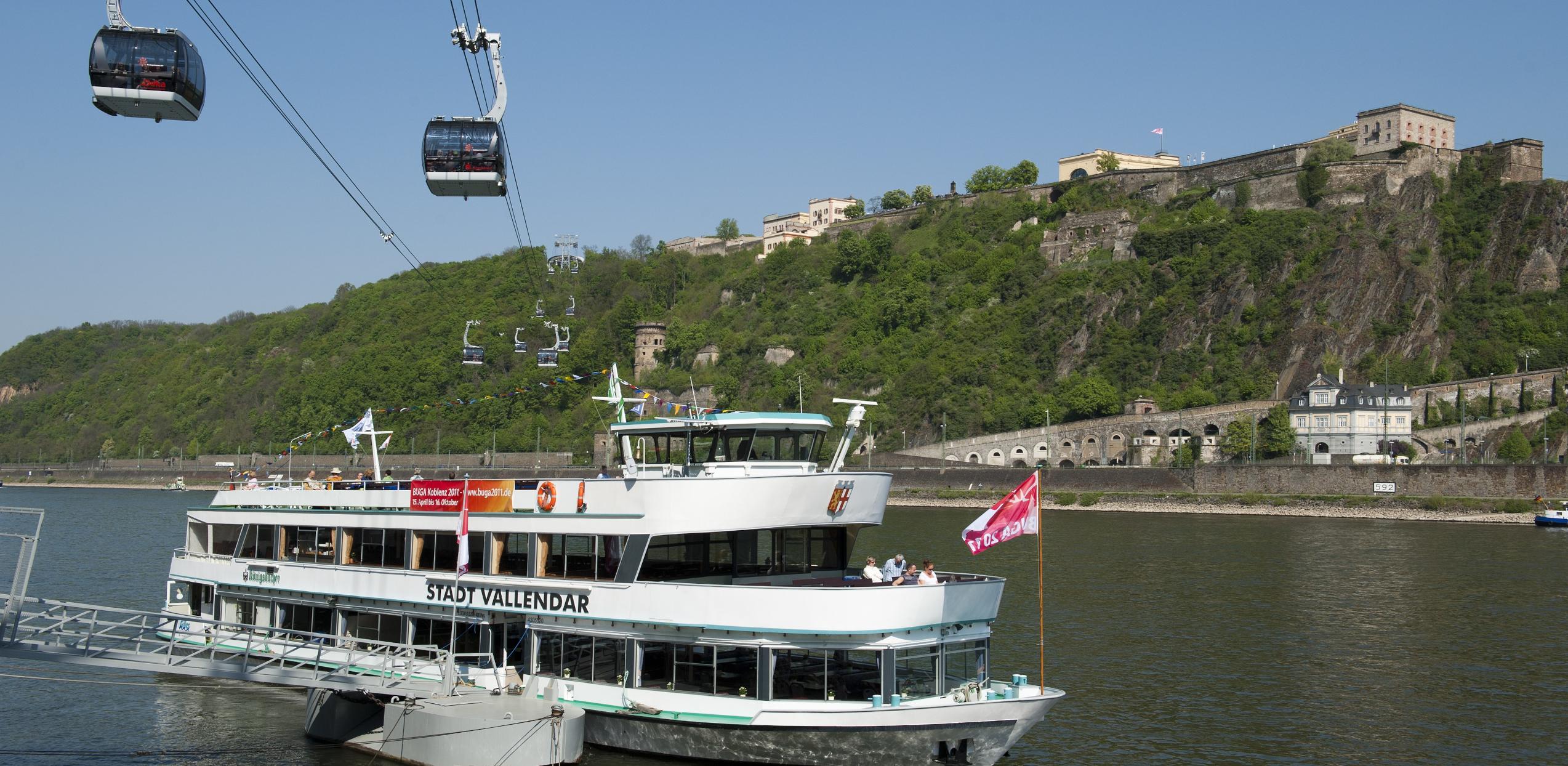 Auf dem Bild ist die Seilbahn aus Koblenz abgebildet. Im Vordergrund ist ein Ausflugsschiff zu sehen. Im Hintergrund sieht man die Festung Ehrenbreitstein